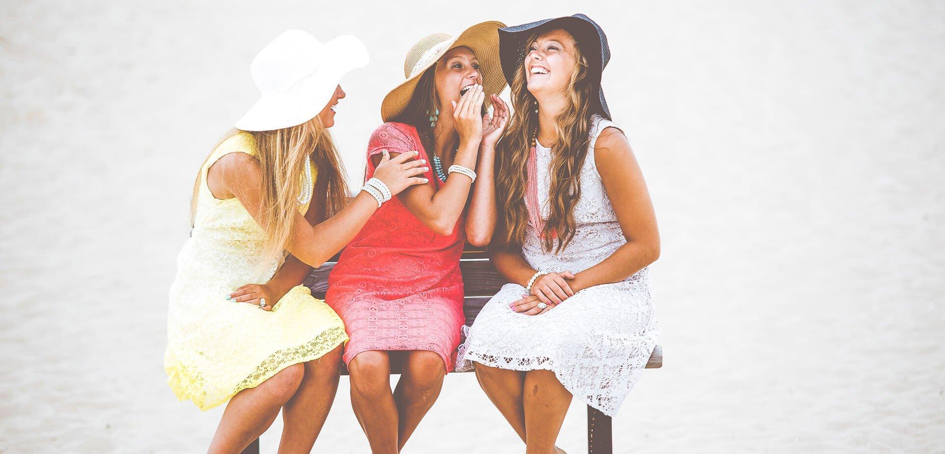 Trio d'amies assises sur un banc en riant par une belle journée ensoleillée