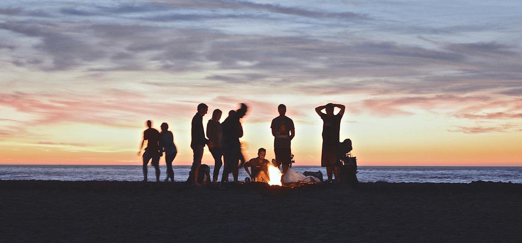 Groupe d'amis autour d'un feu sur une plage devant un coucher de soleil