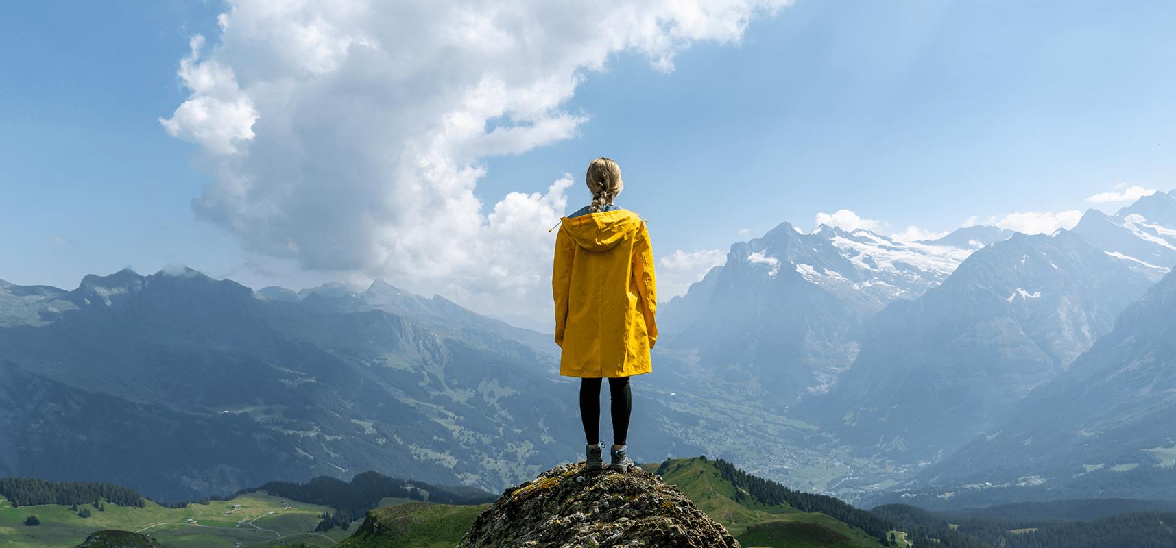 Jeune patiente dans les alpes qui profite de sa nouvelle vue