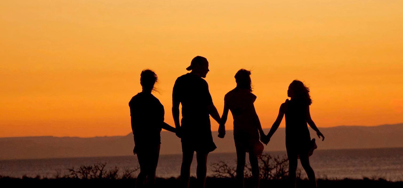 Famille devant un coucher de soleil main dans la main.