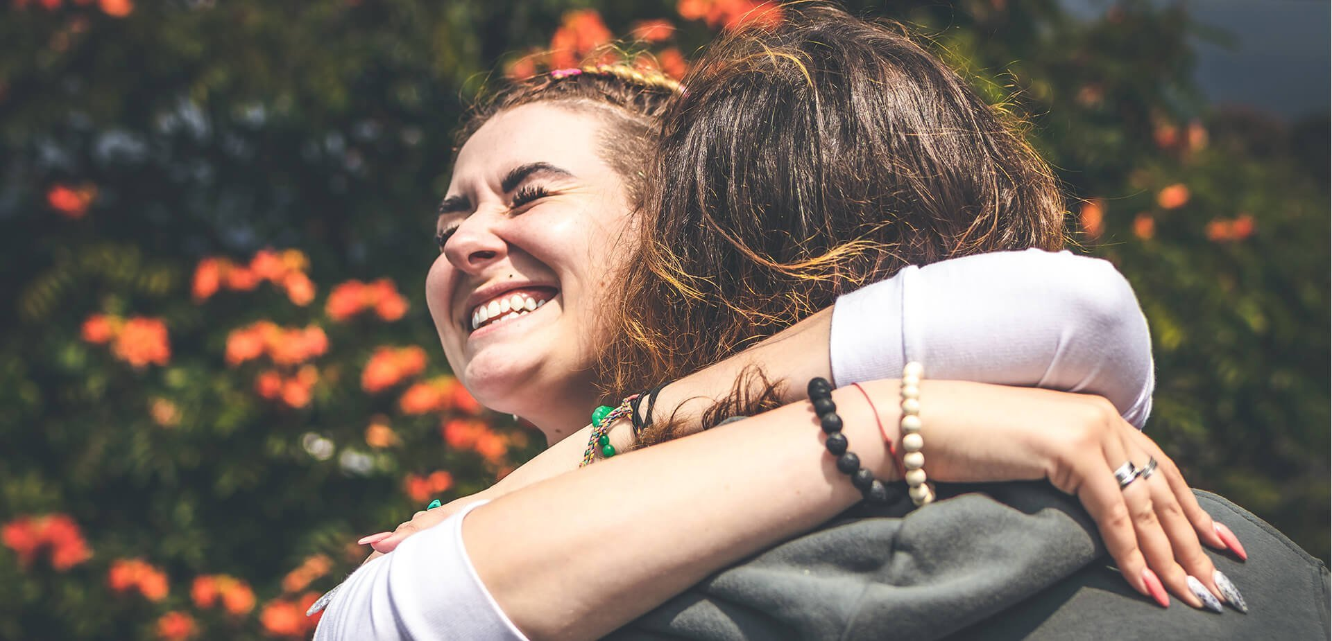Deux amies souriantes qui se serrent dans leurs bras
