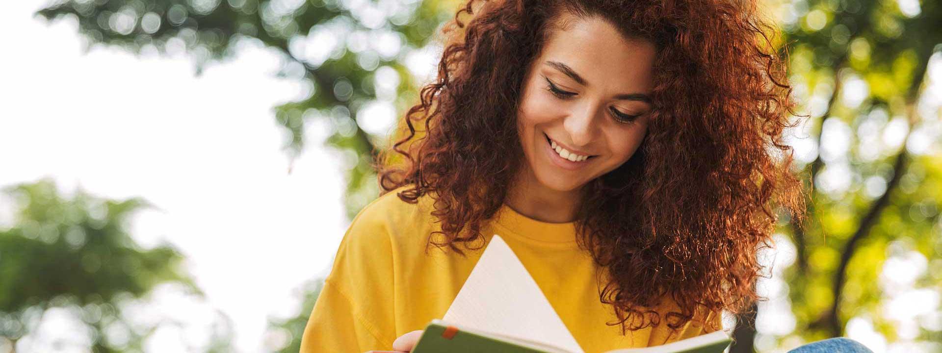 Jeune femme qui lit un livre à l'extérieur
