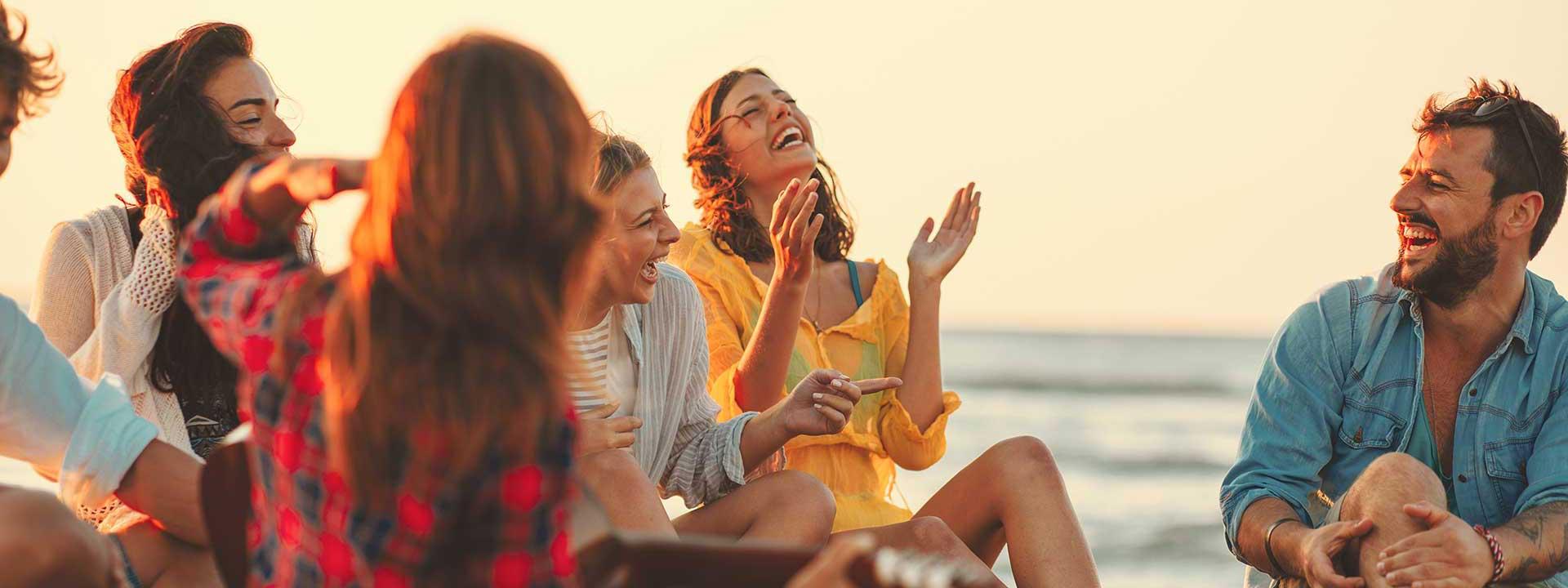 Groupe d'amis qui rient, assis sur une plage